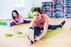 Donna che fa esercizio spaccato dell'incrocio che risolve i suoi muscoli abduttori e legamenti dell'anca Allungamento adatto dell Immagine Stock Libera da Diritti