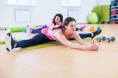 Donna che fa esercizio spaccato dell'incrocio che risolve i suoi muscoli abduttori e legamenti dell'anca Allungamento adatto dell Fotografie Stock