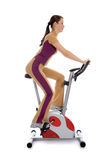 Donna che fa forma fisica su una bici fissa Fotografia Stock