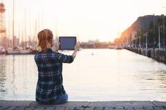 Donna che fa foto sul cuscinetto di tocco di bella vista mentre sedendosi contro il fondo stupefacente del paesaggio del mare con Fotografia Stock