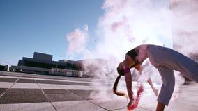 Donna che fa frontflip con i bastoni del fumo stock footage