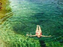 Donna che fa galleggiare in chiaro acqua di un fiume della montagna fotografia stock libera da diritti