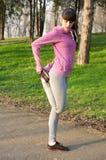 Donna che fa gamba che allunga dopo avere corso nel parco Immagine Stock