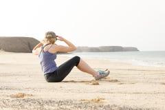 Donna che fa gli allungamenti del torso dalla spiaggia Fotografia Stock