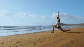 Donna che fa gli allungamenti della gamba Ragazza di forma fisica che allunga le gambe su addestramento della spiaggia Movimento  archivi video
