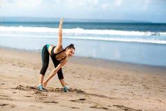 Donna che fa gli esercizi che si scaldano prima del trotto Immagini Stock