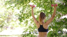 Donna che fa gli esercizi con la testa di legno nel parco video d archivio