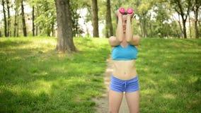 Donna che fa gli esercizi con la testa di legno nel parco stock footage