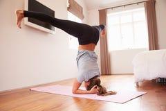 Donna che fa gli esercizi di forma fisica di yoga su Mat In Bedroom fotografia stock