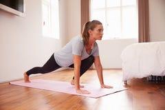 Donna che fa gli esercizi di forma fisica di yoga su Mat In Bedroom fotografie stock