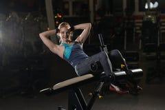 Donna che fa gli esercizi di forza per i muscoli dell'ABS Immagini Stock Libere da Diritti