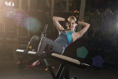 Donna che fa gli esercizi di forza per i muscoli dell'ABS Fotografie Stock