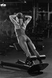 Donna che fa gli esercizi di forza per i muscoli dell'ABS Immagine Stock
