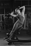 Donna che fa gli esercizi di forza per i muscoli dell'ABS Fotografia Stock Libera da Diritti