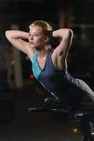 Donna che fa gli esercizi di forza per i muscoli dell'ABS Immagini Stock