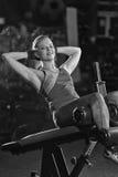 Donna che fa gli esercizi di forza per i muscoli dell'ABS Fotografia Stock