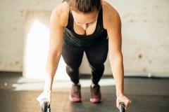 Donna che fa gli esercizi di spinta-UPS sui kettlebells Addestramento adatto dell'incrocio Fotografie Stock Libere da Diritti
