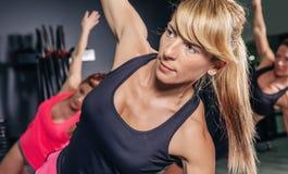 Donna che fa gli esercizi nella classe aerobica con la a Immagine Stock