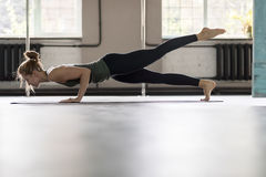 Donna che fa gli esercizi in palestra, allungamento di yoga di addestramento della ragazza di forma fisica di sport Immagine Stock