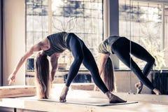 Donna che fa gli esercizi in palestra, allungamento di yoga di addestramento della ragazza di forma fisica di sport Fotografia Stock