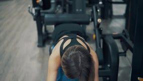 Donna che fa gli esercizi per le gambe ed i muscoli delle natiche in palestra video d archivio