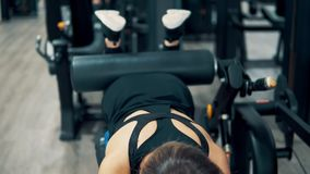 Donna che fa gli esercizi per le gambe ed i muscoli delle natiche in palestra stock footage