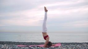 Donna che fa headstand sulla spiaggia sulla stuoia di yoga video d archivio