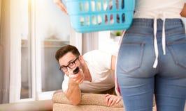 Donna che fa i lavoretti mentre uomo che guarda TV fotografie stock libere da diritti