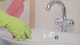 Donna che fa i lavoretti in stanza da bagno nel paese, pulendo dispersore e rubinetto con il detersivo dello spruzzo sequenza stock footage