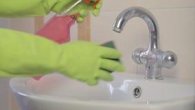 Donna che fa i lavoretti in stanza da bagno nel paese, pulendo dispersore e rubinetto con il detersivo dello spruzzo sequenza video d archivio