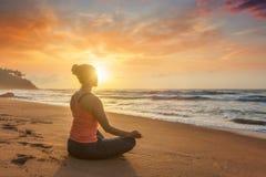 Donna che fa i oudoors alla spiaggia - posa di yoga del loto di Padmasana fotografie stock libere da diritti
