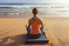 Donna che fa i oudoors di posa di Lotus di yoga alla spiaggia immagini stock