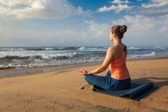 Donna che fa i oudoors di posa di Lotus di yoga alla spiaggia fotografie stock