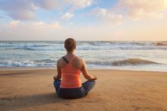 Donna che fa i oudoors di posa di Lotus di yoga alla spiaggia immagini stock libere da diritti