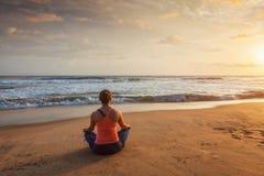 Donna che fa i oudoors di posa di Lotus di yoga alla spiaggia fotografia stock