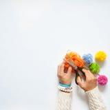 Donna che fa i pompon colorati Vista da sopra Priorità bassa bianca Fotografia Stock