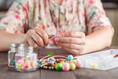 Donna che fa il bijouterie domestico di arte del mestiere fotografie stock libere da diritti