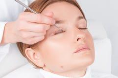 Donna che fa la laminazione, macchiatura, arricciatura, laminazione ed estensione dei cigli per le sferze fotografia stock