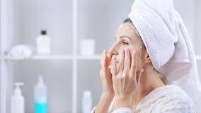 Donna che fa la maschera di protezione antinvecchiamento cosmetica in bagno video d archivio