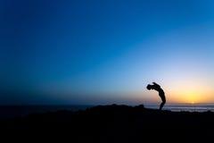 Donna che fa la siluetta di tramonto di yoga Fotografie Stock