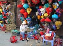 Donna che fa le lanterne davanti al loro negozio al mercato immagine stock