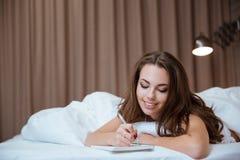 Donna che fa le note in blocco note mentre trovandosi sul letto Fotografia Stock Libera da Diritti