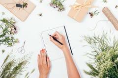 Donna che fa le note fra i fiori ed i regali fertili immagini stock