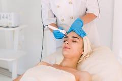 Donna che fa le procedure cosmetiche nella clinica della stazione termale fotografia stock