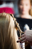 Donna che fa le trecce allo studio dei capelli Fotografia Stock