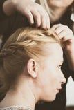 Donna che fa le trecce allo studio dei capelli Immagine Stock