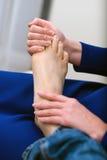 Donna che fa massaggio del piede Fotografie Stock Libere da Diritti