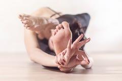 Donna che fa meditazione di yoga e che allunga gli esercizi che piegano in avanti con la sua gamba dietro la testa Fotografie Stock Libere da Diritti