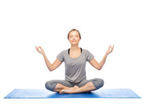 Donna che fa meditazione di yoga nella posa del loto sulla stuoia Immagine Stock