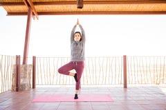 Donna che fa meditazione nella posa di yoga dell'albero Fotografie Stock Libere da Diritti